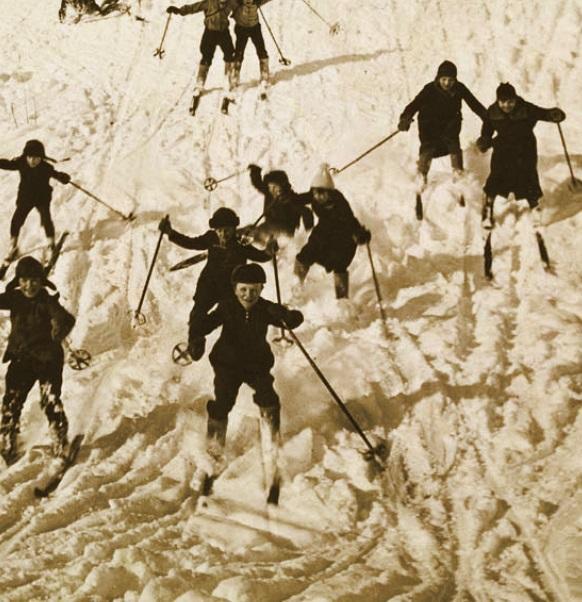 Kuvituskuva lapsista ja nuorista laskemassa mäkeä suksilla 1940–1950-luvulla.